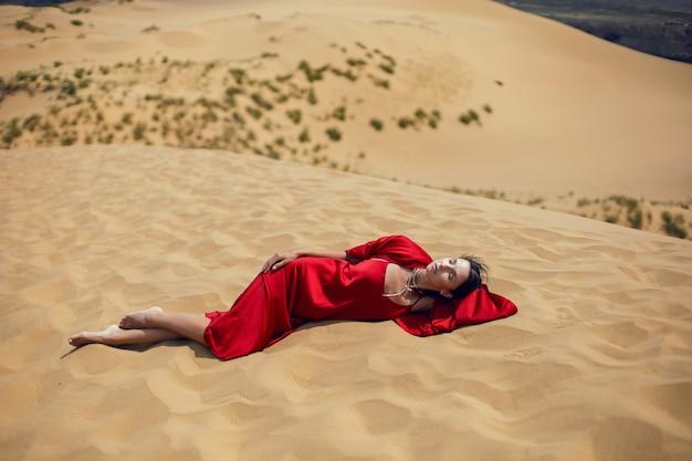 Femme brune sexy dans une longue robe rouge s'asseoir sur une dune en été au daghestan