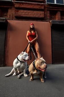 Femme brune sexy et forte posant avec un chien intimidateur dans la rue de la ville, regardant la caméra.