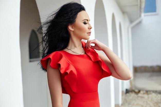 Femme brune sexy en robe rouge se dresse près des murs des vieilles villas au bord de la mer