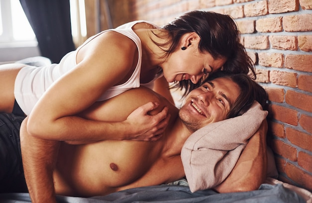 Femme brune sexy en sous-vêtements allongée sur le lit avec son amant.