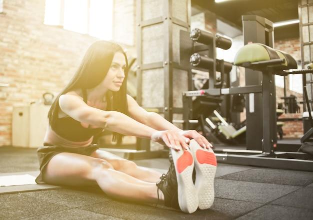 Femme brune sexy sportive en tenue de sport faisant des exercices d'étirement pour les mains et les jambes (tirant les mains vers les jambes) tout en étant assis sur un tapis dans une salle de sport