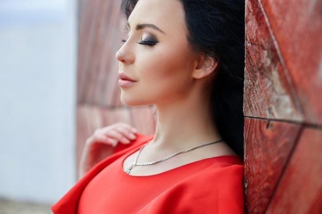 Une femme brune sexy vêtue d'une robe rouge se tient près de la porte rouge. le vent souffle les cheveux, look romantique, délicat, look sexy, beaux yeux. fille se reposant en vacances de voyage d'été