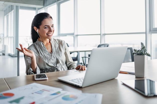 Femme brune souriante détendue dans des écouteurs profitant de la bonne musique à l'aide d'une application pour ordinateur portable en co-travail, un employé de bureau heureux portant des écouteurs se repose, écoutant de nouvelles pistes au travail pendant la pause