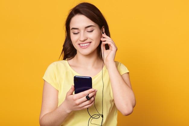 Femme brune souriante, écouter de la musique via un téléphone intelligent moderne et des écouteurs