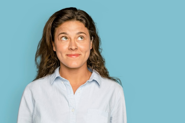 Femme brune souriante sur fond bleu