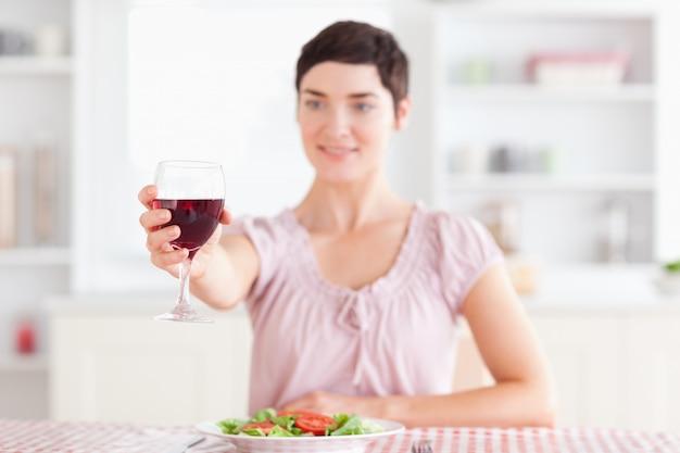 Femme brune souriante grillage avec du vin
