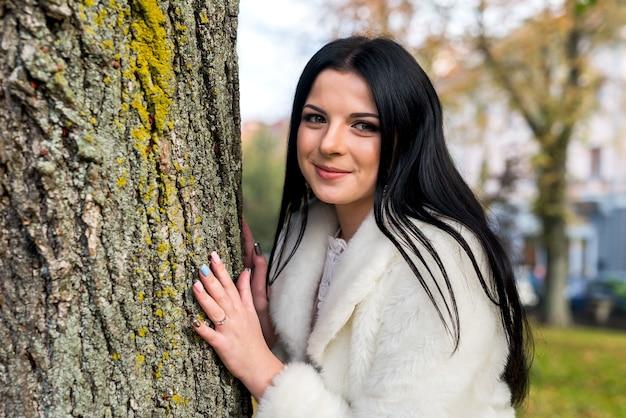 Femme brune souriante posant près du tronc d'un arbre