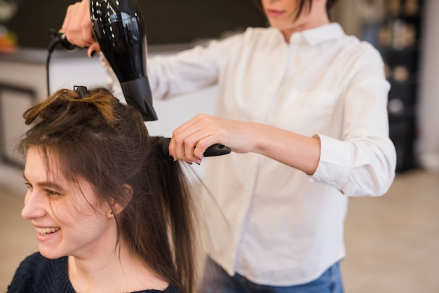 Femme brune souriante se coiffant