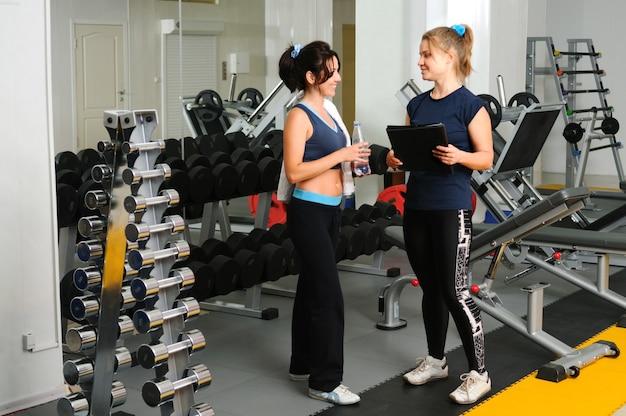 Femme brune souriante avec une serviette et une bouteille d'eau dans les mains consulte un entraîneur de fitness au gymnase