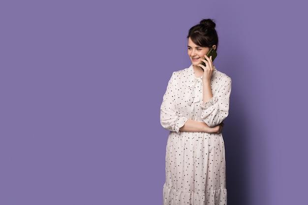 Une femme brune sourit en posant dans une robe sur un mur bleu avec de l'espace libre tout en ayant un téléphone...