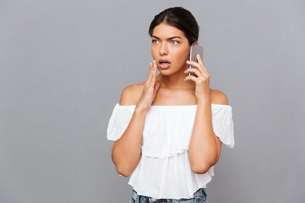 Femme brune surprise parlant au téléphone isolée sur un mur gris