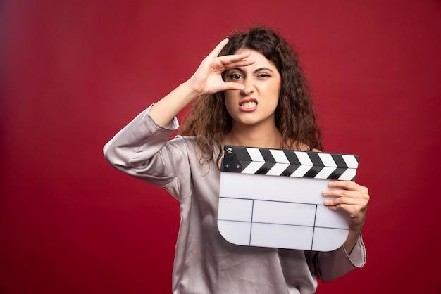 Femme brune tenant clap et faire des grimaces.