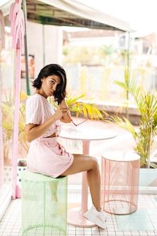 Femme brune tenant des lunettes de soleil dans un café en plein air. ludique jeune femme posant le matin d'été.