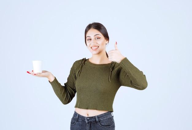 Femme brune tenant une tasse en plastique et donnant les pouces vers le haut.