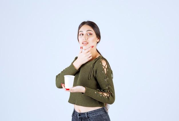 Femme brune tenant une tasse en plastique et pensant.