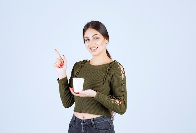 Femme brune tenant une tasse en plastique et pointant quelque part.