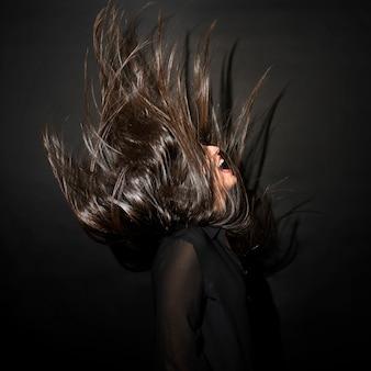 Femme brune en tenue de soirée avec des cheveux venteux