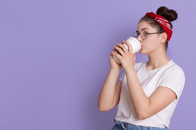 Une femme brune tient et boit du café à emporter, apprécie une boisson agréable, porte un t-shirt décontracté blanc et un bandeau de cheveux, se concentre de côté, apprécie une boisson chaude