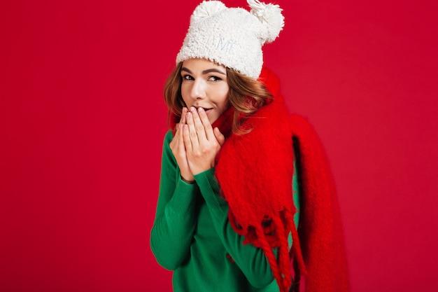 Femme brune très souriante en pull, chapeau et écharpe drôle