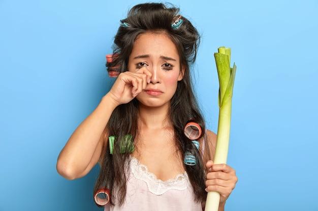 Une femme brune triste et mécontente se frotte les yeux en pleurant, a gâté le maquillage, tient des poireaux frais, étant de mauvaise humeur