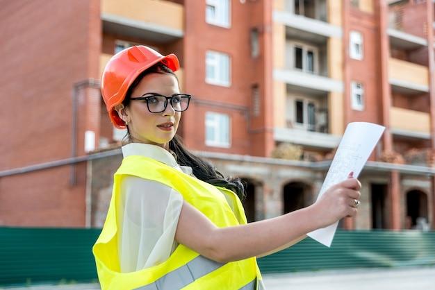 Femme brune en uniforme examinant le plan de construction