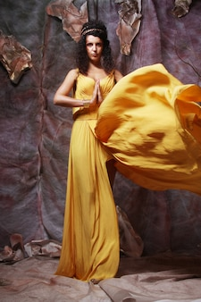 Femme brune vêtue d'une robe de soirée jaune