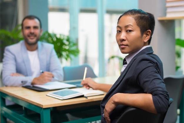 Femme brutale confiante, assise à la table et regardant la caméra