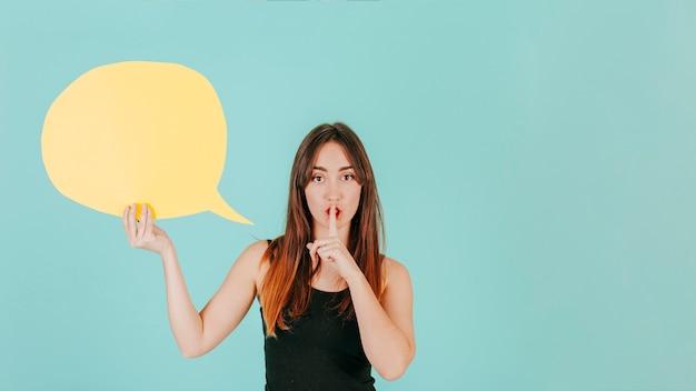 Femme avec bulle de dialogue montrant le geste de silence