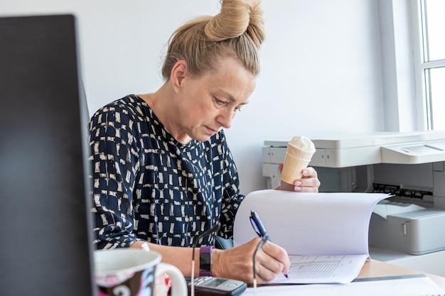 Une femme de bureau d'âge moyen occupée mange de la crème glacée sur son lieu de travail sans interrompre le travail