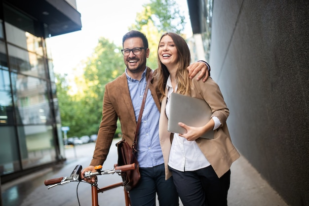 Femme de bureau heureuse avec un couple d'hommes d'affaires profitant d'une pause tout en parlant de flirter en plein air