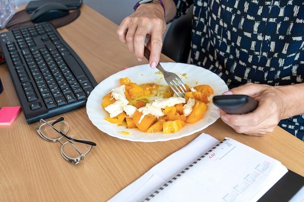 Une femme de bureau occupée déjeune sur son lieu de travail sans interrompre le travail, une assiette avec des aliments sains sur le bureau, vue de dessus