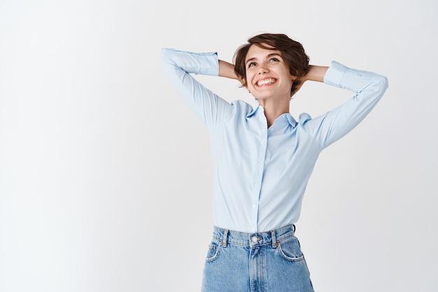 Femme de bureau rêvant de vacances, l'air détendu et souriant, tenant les mains derrière la tête et se reposant du travail, debout sur un mur blanc