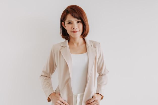 Femme de bureau en vêtements blancs et costume décontracté crémeux sur fond blanc