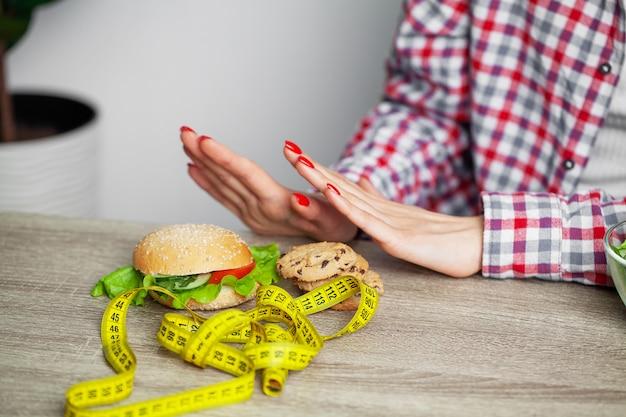 Femme avec burger et ruban à mesurer pendant un régime