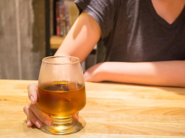 Femme buvant une boisson alcoolisée au bar
