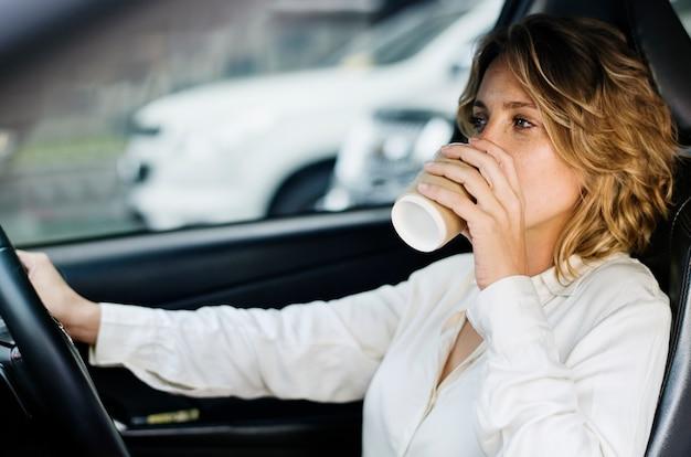 Femme buvant du café dans une voiture