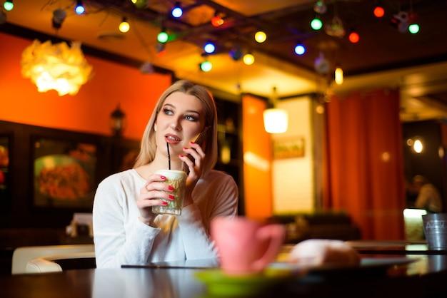 Femme buvant du café et parle au téléphone dans un café.