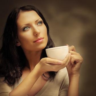 Femme buvant du café (se concentrer sur les yeux du modèle)