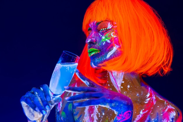 Femme buvant du champagne au néon, discothèque. belle danseuse modèle fille coloré lumineux fluorescent maquillage