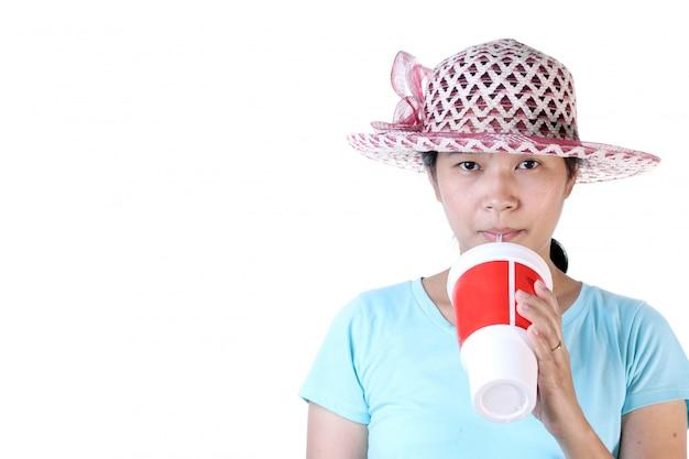 Femme buvant du cola à travers une paille avec verre rouge