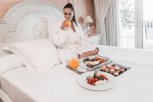 Femme buvant du jus au petit déjeuner au lit