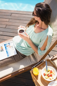 Femme buvant du thé au bord de la piscine avec petit déjeuner sur la table