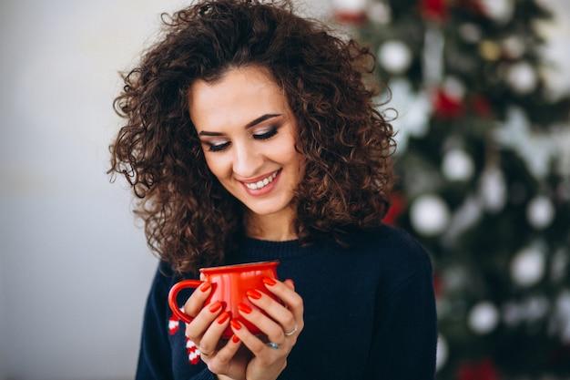 Femme buvant du thé près d'un arbre de noël