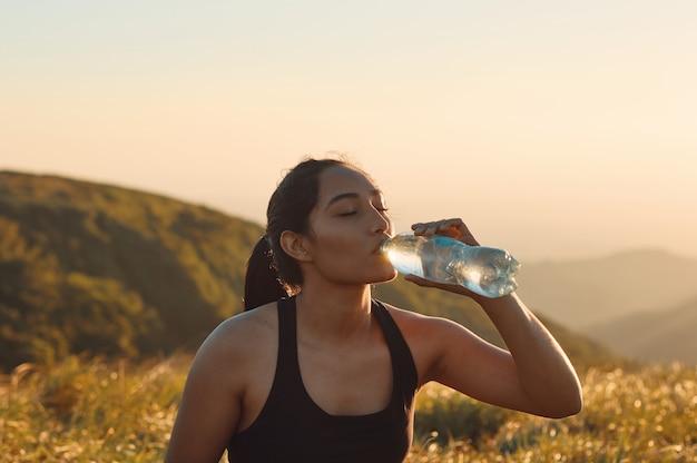 Une femme buvant de l'eau après des activités sportives