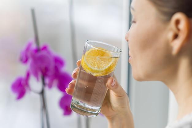Femme buvant de l'eau avec du citron bio frais