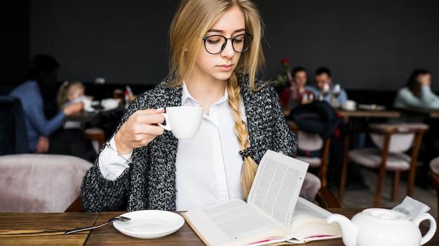 Femme buvant et lisant un livre