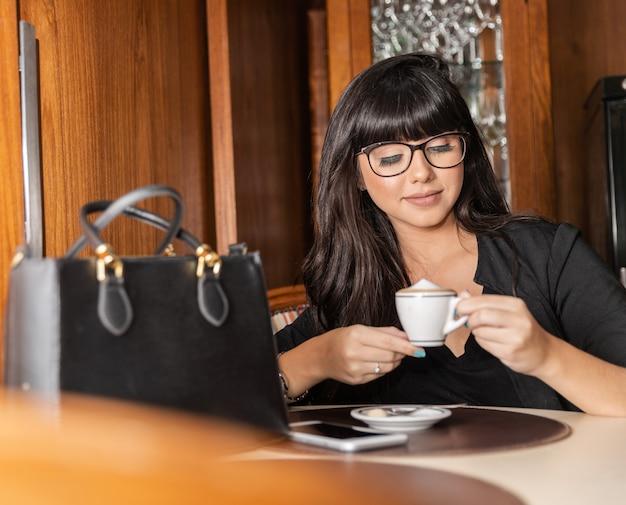 Femme buvant une table basse. les femmes au café.