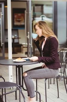Femme buvant une tasse de café au café