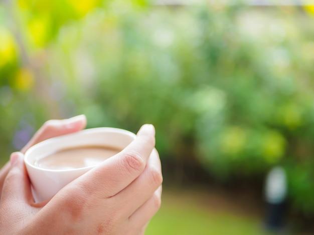 Femme buvant une tasse de café au jardin le matin