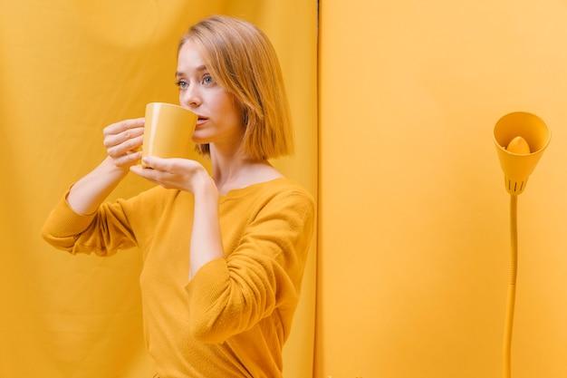 Femme buvant à la tasse dans une scène jaune